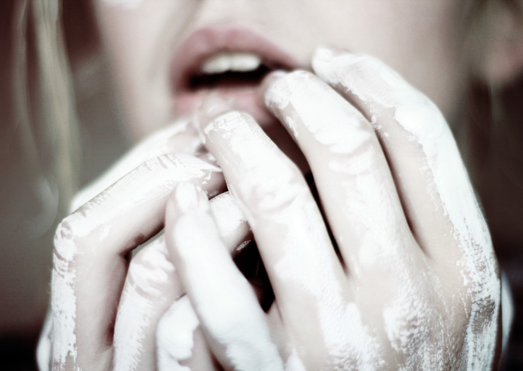 Close-up of white painted hands. Photograph by Noukka Signe.