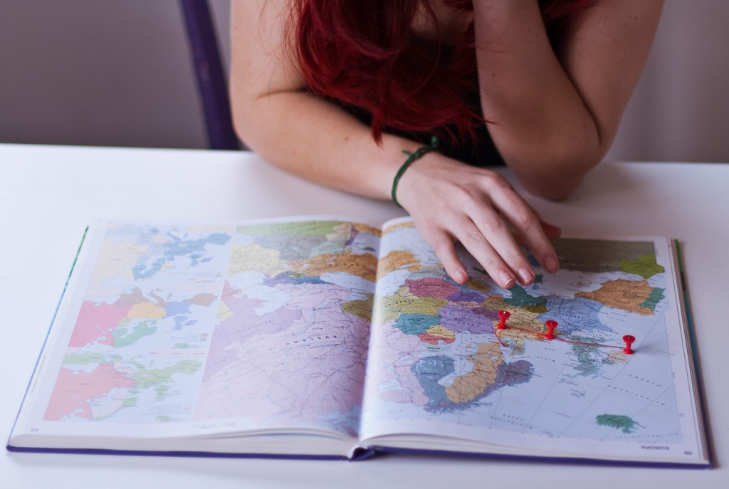 Hand hovering over world map with pins on Europe by Noukka Signe