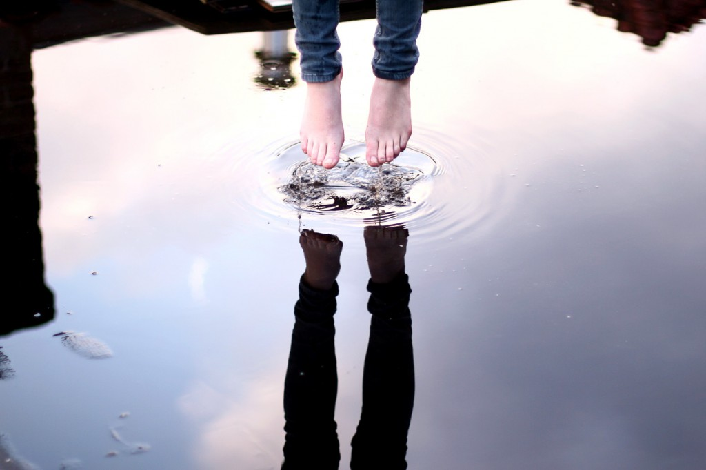 Bare feet jumping in a puddle reflecting the sky