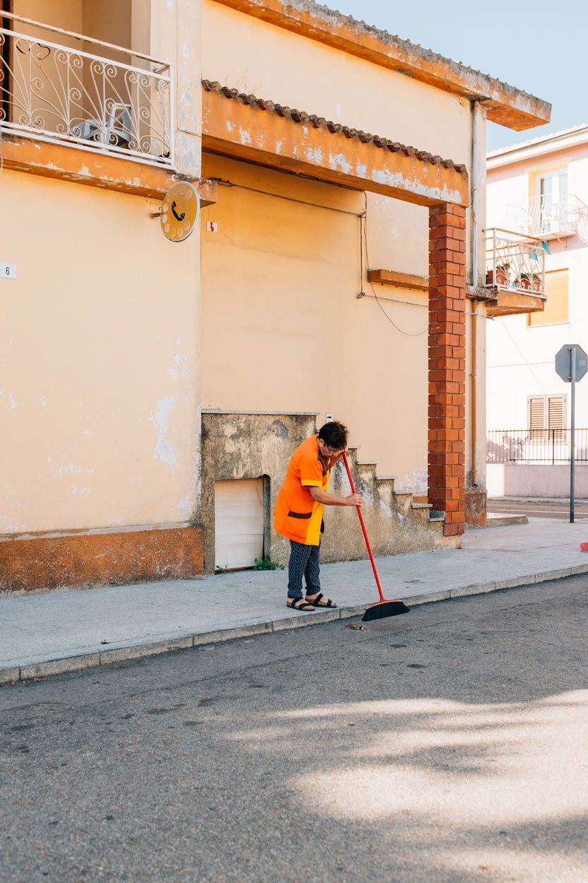 Girasole, woman sweeping street